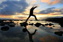 Silueta que salta en la puesta del sol imagen de archivo libre de regalías