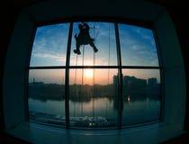 Silueta que trabaja fuera de la ventana Fotos de archivo libres de regalías