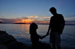 Silueta romántica de los pares sobre fondo de la puesta del sol del mar Foto de archivo libre de regalías