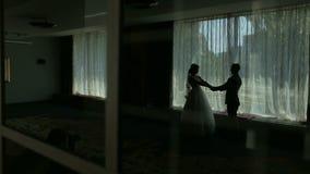 Silueta romántica de los recienes casados cerca de la ventana almacen de video