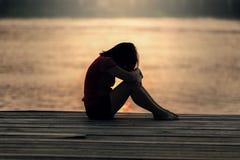 Silueta triste de la mujer preocupante en la puesta del sol Imagen de archivo libre de regalías