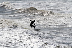 Silueta y ondas de la persona que practica surf Foto de archivo libre de regalías