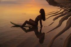 Silueta y reflexión de la muchacha que se sientan en la tabla hawaiana en la playa del océano en fondo de la puesta del sol hermo imagenes de archivo