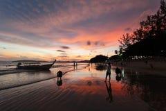 Silueta y reflexión del barco y de la gente contra el cielo de la puesta del sol Imagen de archivo