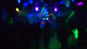 Siluetas borrosas de la gente de baile en un club nocturno bajo luz coloreada de proyectores metrajes