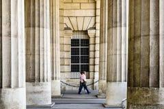 Siluetas borrosas de los turistas que caminan entre las columnas majestuosas enormes del edificio viejo foto de archivo libre de regalías
