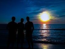 3 siluetas con puesta del sol en el fondo Imagen de archivo