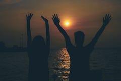 Siluetas de abrazar pares contra el mar en la puesta del sol Imagen de archivo libre de regalías