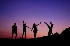 Siluetas de amigos en la puesta del sol Fotografía de archivo libre de regalías
