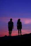 Siluetas de amigos en la puesta del sol Fotos de archivo