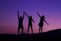Siluetas de amigos en la puesta del sol Imagen de archivo libre de regalías