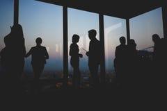 Siluetas de diversos grupos de empresarios que hablan con uno a en interior de la oficina del rascacielos imagenes de archivo