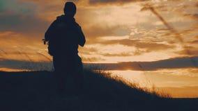 Siluetas de dos caminantes con las mochilas que disfrutan de la opini?n de la puesta del sol del top de una monta?a Disfrutar de  metrajes