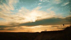 Siluetas de dos caminantes con las mochilas que disfrutan de la opini?n de la puesta del sol del top de una monta?a Disfrutar de  almacen de video