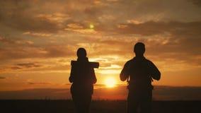 Siluetas de dos caminantes con las mochilas que disfrutan de la opini?n de la puesta del sol del top de una monta?a Disfrutar de  almacen de metraje de vídeo