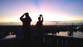 Siluetas de dos personas en la puesta del sol La gente toma las fotografías de una puesta del sol hermosa de un edificio alto Foto de archivo libre de regalías