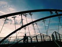 Siluetas de dos personas que caminan en el puente de Frankston en Melbour Imagen de archivo libre de regalías