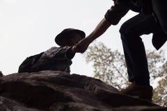 Siluetas de dos personas que suben en la montaña y que ayudan, ayuda imágenes de archivo libres de regalías