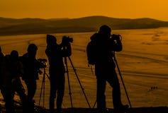Siluetas de fotógrafos, con su equipo, tirando una puesta del sol imagen de archivo libre de regalías