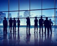 Siluetas de hombres de negocios en un edificio de oficinas Foto de archivo libre de regalías