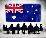 Siluetas de hombres de negocios y una bandera de Australia Foto de archivo libre de regalías