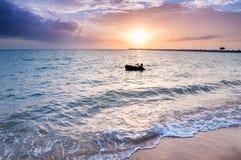 Siluetas de la actividad en la playa durante puesta del sol Foto de archivo