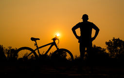 Siluetas de la bici de montaña con el hombre Imágenes de archivo libres de regalías