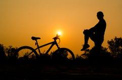 Siluetas de la bici de montaña con el hombre Fotografía de archivo