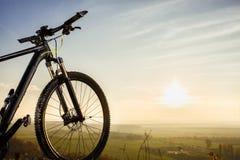 Siluetas de la bicicleta con el cielo y el sol Foto de archivo