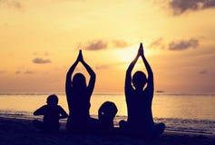 Siluetas de la familia que hacen yoga en la puesta del sol Foto de archivo libre de regalías