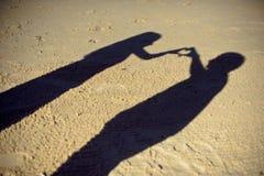 Siluetas de la fotografía de los pares o de dos amantes junto, sombra en la tierra, gesto de la mujer un brazo en forma de corazó imágenes de archivo libres de regalías