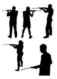 Siluetas de la gente con el arma foto de archivo libre de regalías