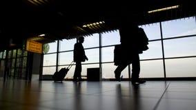 Siluetas de la gente con las maletas que se mueven al pasillo de la salida en el aeropuerto almacen de video