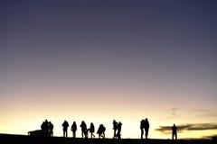 Siluetas de la gente contra el cielo nocturno Fotografía de archivo