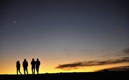 Siluetas de la gente contra el cielo nocturno Fotos de archivo libres de regalías