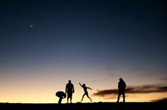 Siluetas de la gente contra el cielo nocturno Imagen de archivo