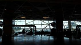 Siluetas de la gente en café en terminal de aeropuerto con las ventanas panorámicas metrajes