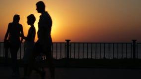 Siluetas de la gente en la calle Puesta del sol en el mar Vídeo colocado metrajes