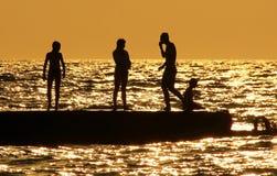 Siluetas de la gente en el mar en la reclinación de la familia de la puesta del sol Foto de archivo
