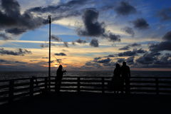 Siluetas de la gente en la puesta del sol en el mar Fotos de archivo libres de regalías