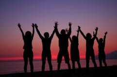 Siluetas de la gente en puesta del sol Fotografía de archivo libre de regalías