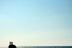Siluetas de la gente en un acantilado sobre el mar Imagen de archivo