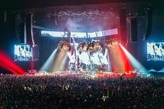 Siluetas de la gente en un brillante en el concierto de rock del estallido delante de la etapa Manos con los cuernos del gesto Es Imagenes de archivo