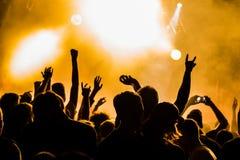 Siluetas de la gente en un brillante en el concierto de rock del estallido delante de la etapa Manos con los cuernos del gesto Es fotografía de archivo libre de regalías