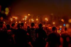 Siluetas de la gente irreconocible de nuevo a nosotros en un festival de la noche, una demostración con música y los fuegos artif fotografía de archivo libre de regalías