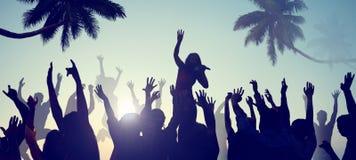 Siluetas de la gente joven en un concierto de la playa Foto de archivo libre de regalías