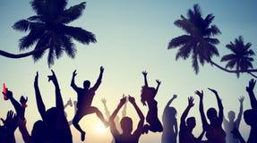 Siluetas de la gente joven que celebra en una playa Imágenes de archivo libres de regalías