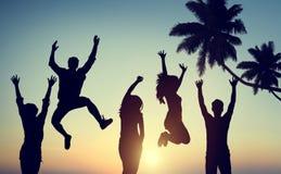 Siluetas de la gente joven que salta con el entusiasmo imagenes de archivo