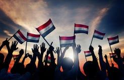 Siluetas de la gente que agita la bandera de Iraq Fotografía de archivo