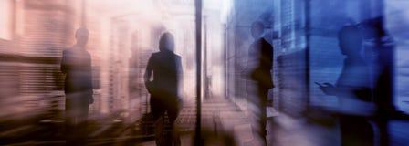 Siluetas de la gente que camina en la calle cerca de rascacielos y de edificios de oficinas modernos Imagen borrosa de la exposic imagenes de archivo